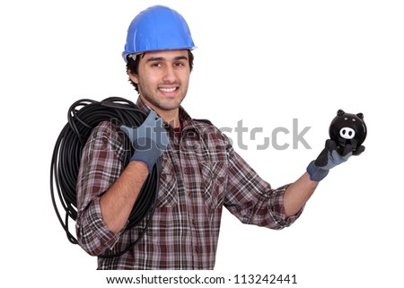 Tradesman holding electric cabling and a piggy bank