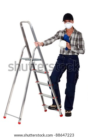 Tradesperson holding a spray gun and standing next to a stepladder