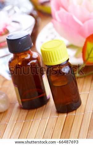 Tradicional alternative theraphy or medicine,  concept of healthy lifestyle, aromatherapy.Two bottles of aromatic oil with flowers in a background