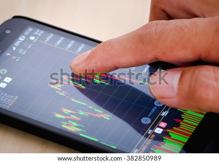 Trading on stock market with smartphone. Closeup photo.