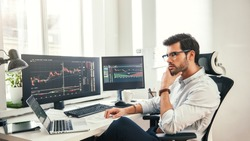 Trading online. Successful and young bearded trader in eyeglasses and formal wear working with laptop while sitting in his office in front of computer screens with trading charts