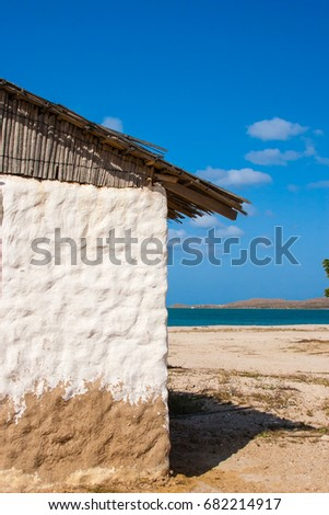 Traditional adobe house next to the sea under blue sky #682214917