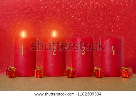 traditional advent candles with numbers and gifts on red background #1102309304