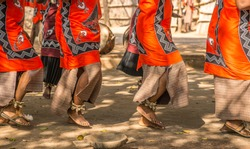Traditional African dancers on sandals dance outdoors in brightly colored clothing. They are accompanied by drums and singing
