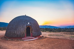 Traditional African Rondavel with Thatch Roofing in Eswatini (Swaziland). Example of Ethnic Tribal Housing with Beautiful Sunset and Mountains in Distance.