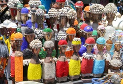 Traditional African wooden handmade dolls with seashells and colorful bead decoration at local craft market, Cape Town, South Africa. Souvenirs from Africa