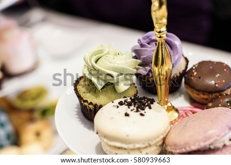 traditional afternoon high tea in hotel with Macaroons and cupcake sweets #580939663