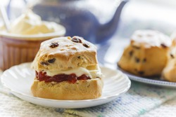 Traditional afternoon tea with scones, jam and cream, blue teapot and crockery, light and summery teashop menu