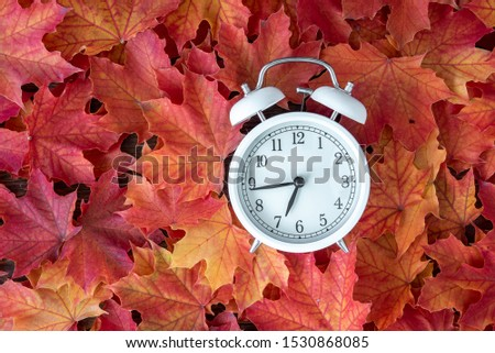 Traditional alarm clock on a background of orange and yellow maple leaves, fall time change concept