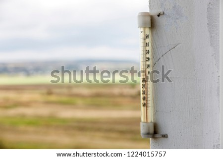 Traditional alcohol glass thermometer Celsius attached to plastered white wall showing warm temperature on bright blurred light blue and white outdoors copy space background. Weather forecast concept.