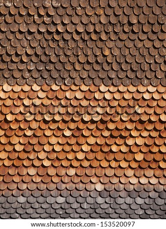 Traditional alpine wooden shingle wall in the sun