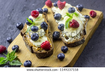 Traditional American and European summer breakfast: sandwiches of toast with peanut butter or cream cheese with raspberries and blueberry, banana. Black concrete table. copy space top view