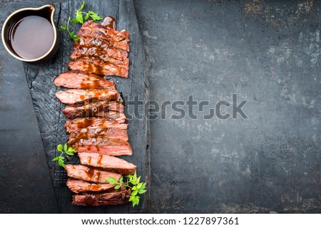 Traditional American barbecue dry aged flank steak sliced with hot sauce and chili as top view on an old carbonized board with copy space right