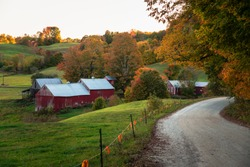 Traditional American farm with a red wooden barn in a rolling autumnal landscape at sunset. Beautiful fall foliage.