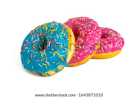 Traditional american glazed donuts with blue and pink icing, sprinkled with colorful sprinkles, isolated on white background