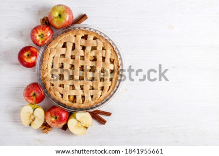 Traditional American Thanks Giving pie, whole & halved apples, cinnamon sticks, anise seeds. Homemade fruit tart baked to golden crust with ingredients. Close up, copy space, top view, background.