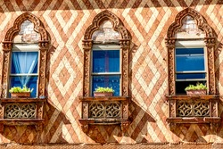 Traditional ancient gothic style window with flower pots in Venice, Italy