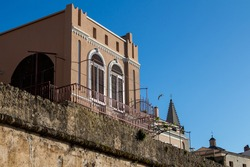 Traditional and still original architecture of a house. Windows with archs. Two towers of the churches in the background. Bright blue sky. Alghero, Sardinia, Italy.