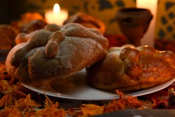 Traditional and sugary bread of the dead on a white glass plate, around it marigold flowers, lighted candles, diffuse background of colored confetti.