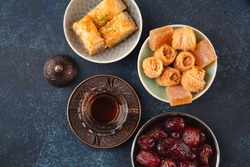 Traditional Arab fresh hot tea time with sweets, baklava, dates, lokum from above. Ramadan snack with Turkish delights and Arabic pastry on blue rustic background top view