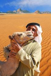 Traditional arab man kissing and hugging a baby camel in Wadi Rum desert, Jordan