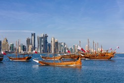 Traditional Arabic Dhow boats with Qatar flags in Doha, Qatar National day preparation. Doha, Qatar, Middle East.
