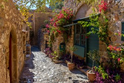 Traditional architecture with  narrow  stone street and a colorfull bougainvillea in  the medieval  castle of Monemvasia, Lakonia, Peloponnese, Greece.