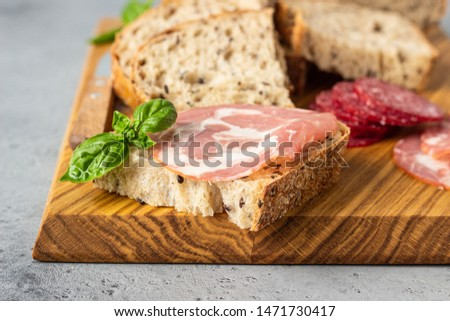 Traditional artisan bread with seeds and pork sausage and salami served on a wooden cutting board. Open sandwich with pork sausage. #1471730417