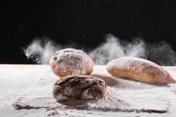 Traditional artisan rye bread loaf fall into flour. Dark background. Bakery and homemade rustic bread concept.