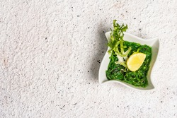 Traditional Asian chukka salad with peanut sauce in a bowl. Meal decorated lemon wedge and herbs. Healthy food concept, light colors stone background, top view