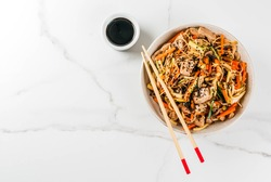 Traditional Asian food. Lunch stirfry: rice noodles, zucchini, carrots, bamboo, mushrooms, pork (beef), soy sauce and black sesame. With soy sauce, chopsticks. Copy space top view
