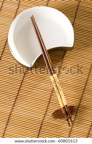 Traditional asian hand made chopsticks and dish on table cover.