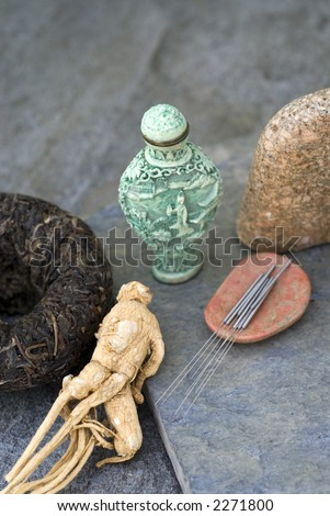 Traditional asian health items:black tea, ginseng, acupuncture needles, and medicine jar.