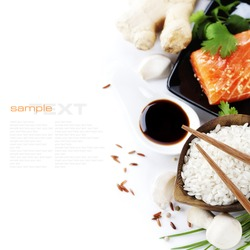 traditional asian ingredients (Fresh salmon steak filet, uncooked rice, ginger, garlic, mushrooms, soy sause and chopsticks) over white with sample text