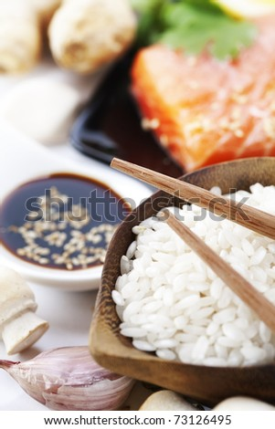 traditional asian ingredients (Fresh salmon steak filet, uncooked rice, ginger, garlic, mushrooms, soy sause and chopsticks) over white