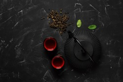 Traditional Asian tea ceremony. Black metal teapot, tea cups, dry tea on a black stone background. Top view, flat lay