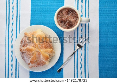 Traditional, authentic, delicious Mexican bread of the dead or dead bread with sugar on a white plate over a typical white and blue tablecloth with a cup of hot cocoa and a fork #1492178723