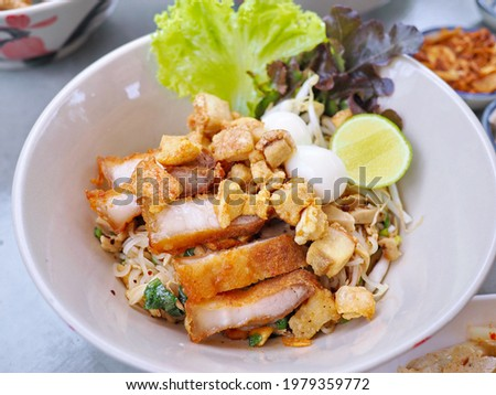 Traditional authentic popular Thai street food as everyday easy cheap meal dried noodles with rice vermicelli, crispy pork belly, pork rinds, pork crackling, boiled egg, lime, red chopsticks Stock photo ©
