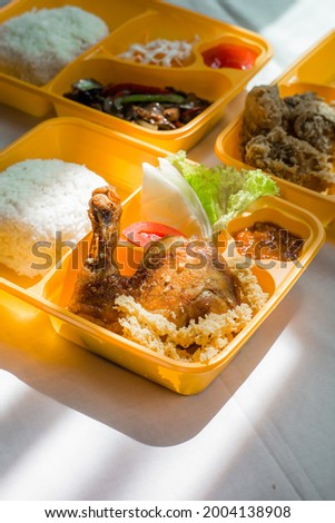 Traditional Ayam kremes set on bento box. indonesian traditional food. fried chicken. chicken bento with vegetables.  Stock fotó ©