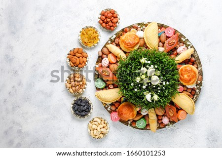 Traditional Azerbaijan holiday Novruz background with green semeni,traditional azerbaijan sweets,shekerbura,qogal,paxlava,mutaki and different nuts and sweets,top view,space for copy