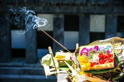 Traditional balinese Canang Sari offerings to gods and spirits with flowers, food and smoky aromatic sticks blurred background. Indonesian culture and religion. Balinese traditional travel concept
