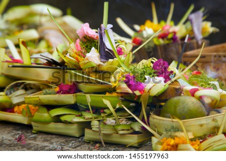 Traditional Balinese Hindu offerings to the gods called Canang sari. Colorful flowers in a tray made of palm leaves are offered daily as a form of thanks for peace given to the world.  Bali, Indonesia