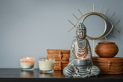 Traditional balinese woven rattan boxes, mirror and buddha statuette  as home decoration on blue background
