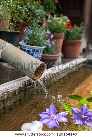 Traditional bamboo fountain with lotus flower decoration.