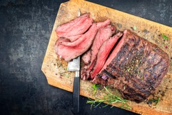 Traditional barbecue dry aged sliced roast beef steak with herbs as top view on an old cutting board with copy space left