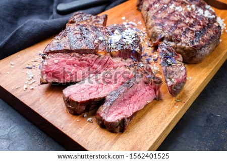 Traditional barbecue dry aged wagyu entrecote beef steak sliced with salt and spice as closeup on modern design wooden cutting board