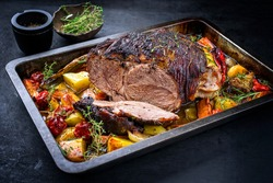 Traditional barbecue lamb roast sliced with tomatoes and fried potatoes as closeup in a metal tray