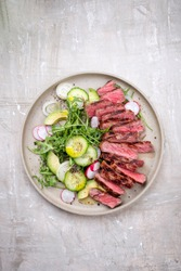 Traditional barbecue skirt steak sliced with salad and avocado as close-up on a plate with copy space