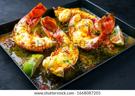 Photo of  Traditional barbecue spiny lobster tail sliced and offered with saffron lemon sauce as closeup in a metal try
