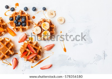 Traditional belgian waffles with fresh fruit and caramel on white background. Flat lay, top view, copy space.